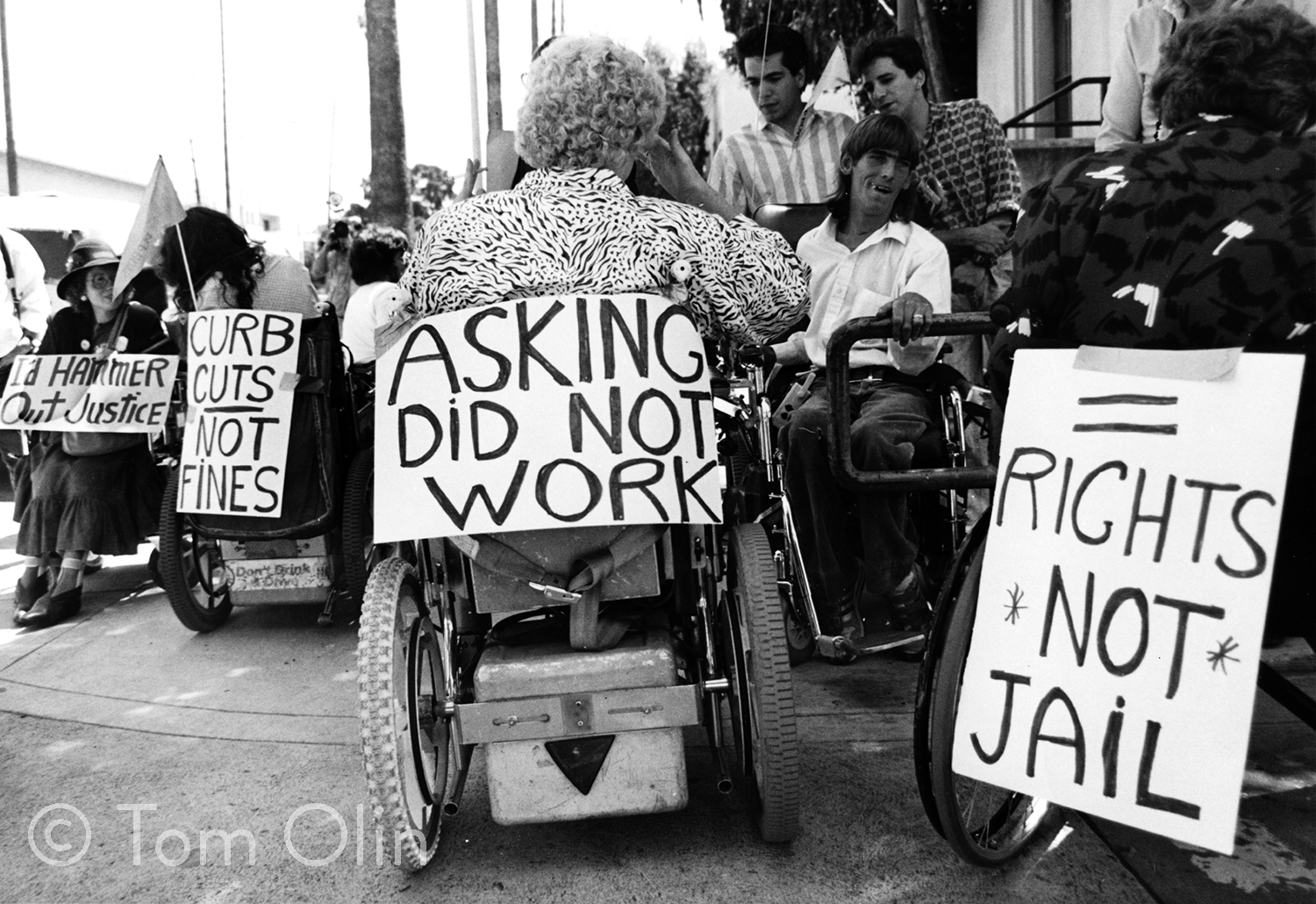 Black and white photograph of several disability activists in wheelchairs. They are holding signs that say I'd hammer out justice, curb cuts not fines, asking did not work, and rights not jail.