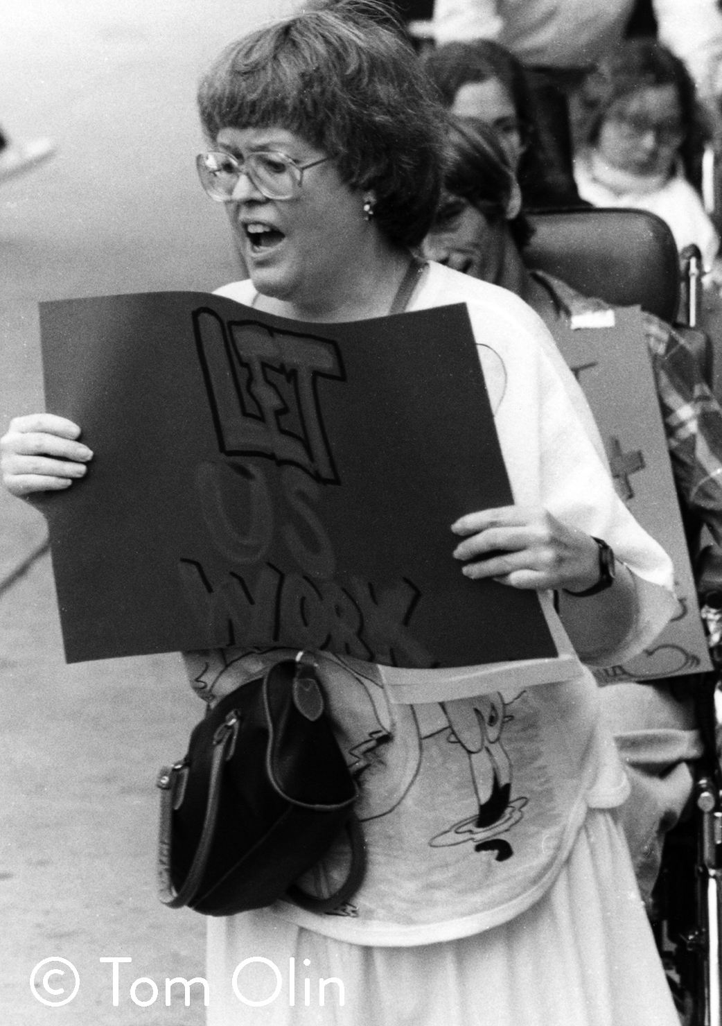 "Black and white photograph of a woman protesting. She's holding a handmade sign that reads ""Let us work"""