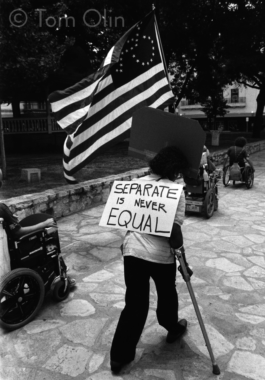 Black and white photograph of several disability rights activists marching on a cobblestone sidewalk. In the foreground, an activist his using a cane and holding a large American flag. Where the fifty stars usually are, there's an outline of the accessibility symbol made of stars. The activist is holding a sign that says separate is never equal. In the background are several people in wheelchairs.