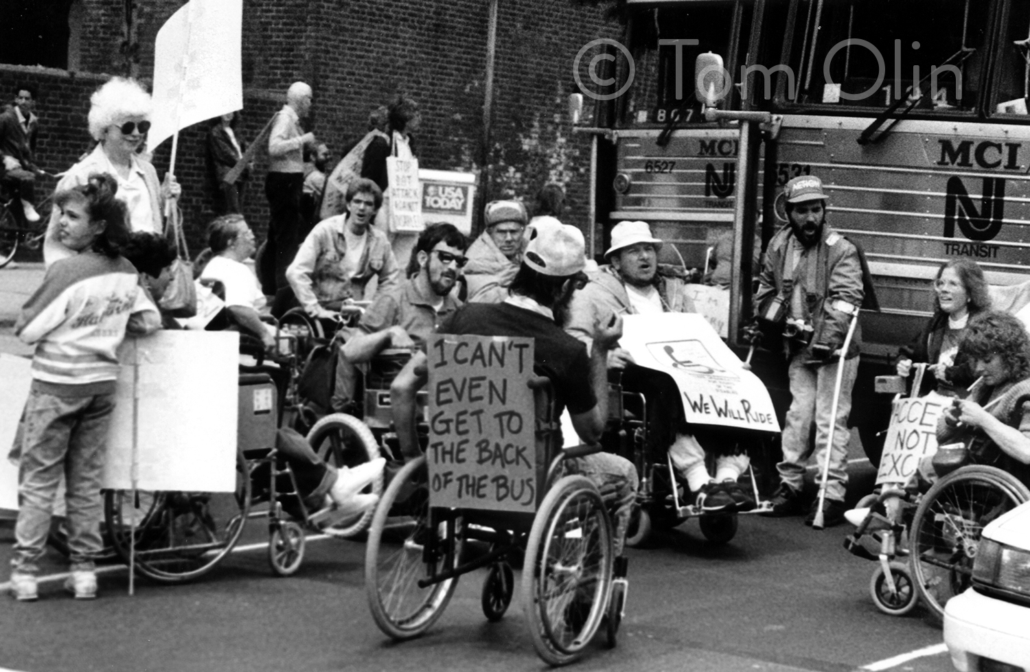 Black and white photo of a group of disability rights activists holding signs. Many are in wheelchairs. In the foreground, a man has a sign on the back of his wheelchair that says I can't even get to the back of the bus.