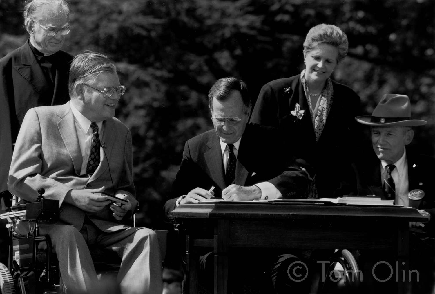 Black and white photograph of President George H.W. Bush sitting at a desk. He's signing the ADA. Next to him and behind him are two men in wheelchairs. Behind him is a woman and a religious leader.