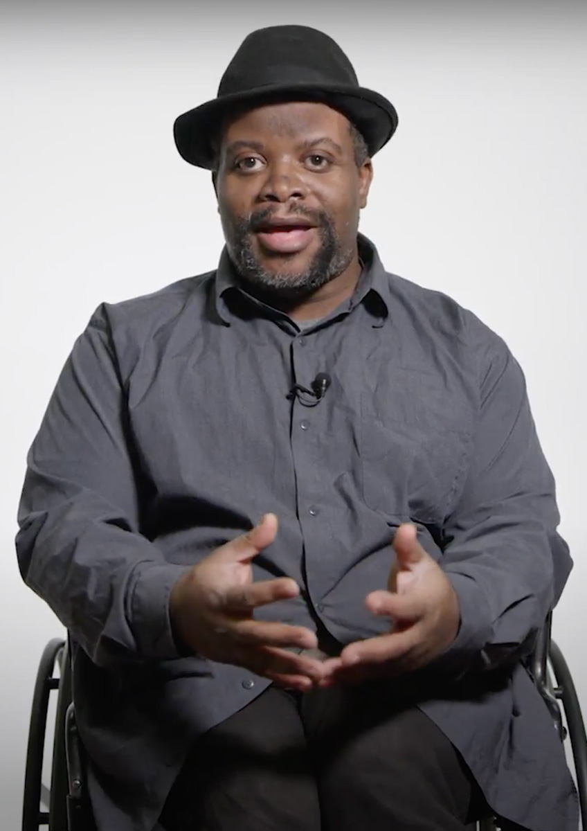 Photograph of David Hale, a Black man in a wheelchair. He's facing the camera in the middle of speaking.