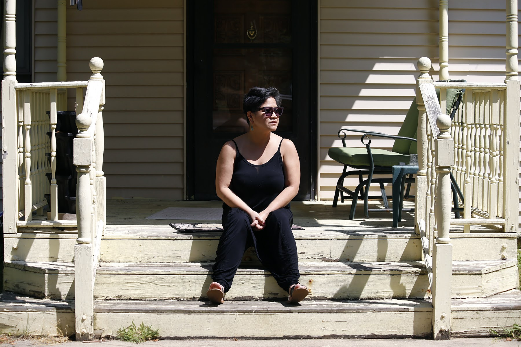 Photograph of Fran Flaherty sitting on the steps leading up to her home.