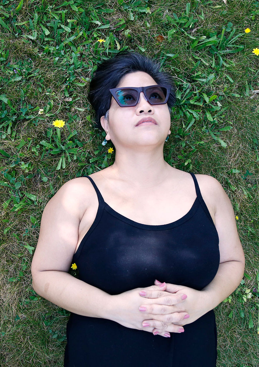 Photograph of essay author Fran Flaherty, a Filipino woman wearing sunglasses and a black jumpsuit. She's lying in the grass with small yellow wildflowers around her.