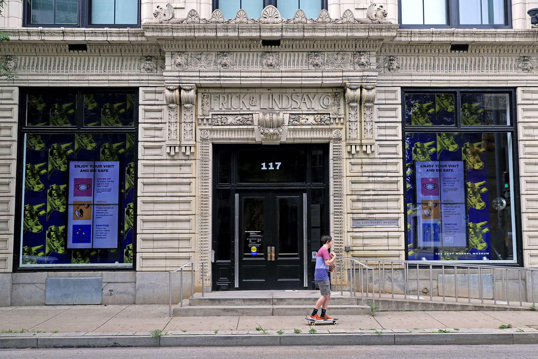 Head-on photograph of the outside of the Andy Warhol Museum. In the windows are large blue and yellow prints of Andy Warhol's cow prints. The entrance has both stairs and a ramp. In the foreground, someone skateboards down the sidewalk.