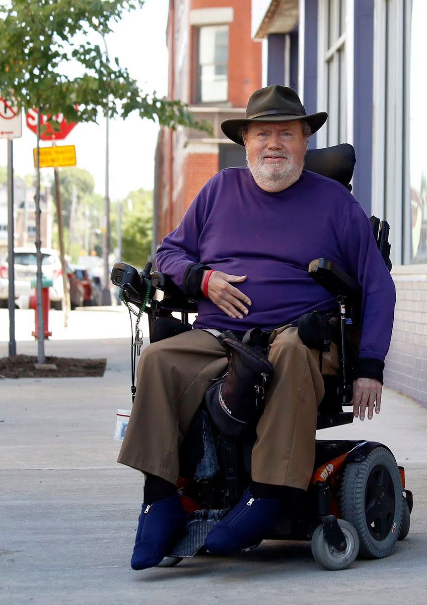 Photograph of essay author John Tague, a white man in sitting in a power wheelchair. He's on the sidewalk facing the camera, wearing a purple sweater and wide hat.