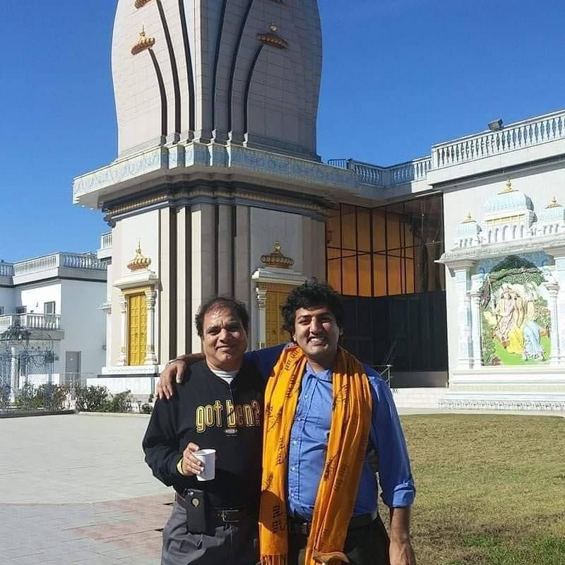 Photograph of two Brown men stand with their arms around each other in front of a Hindu temple. Both are facing the camera. Puneet stands on the right with a big smile on his face.