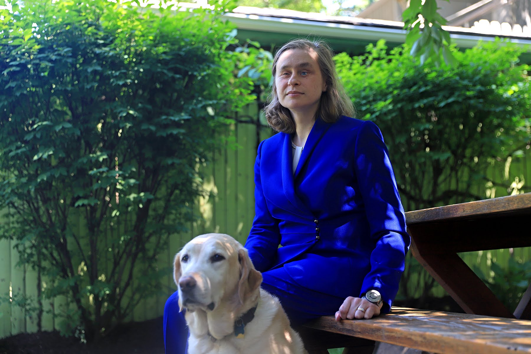 Photograph of essay author Catherine Getchell, a blind woman wearing a blue suit.       She is in her backyard sitting on a wooden bench. Her guide dog is sitting in front of her.