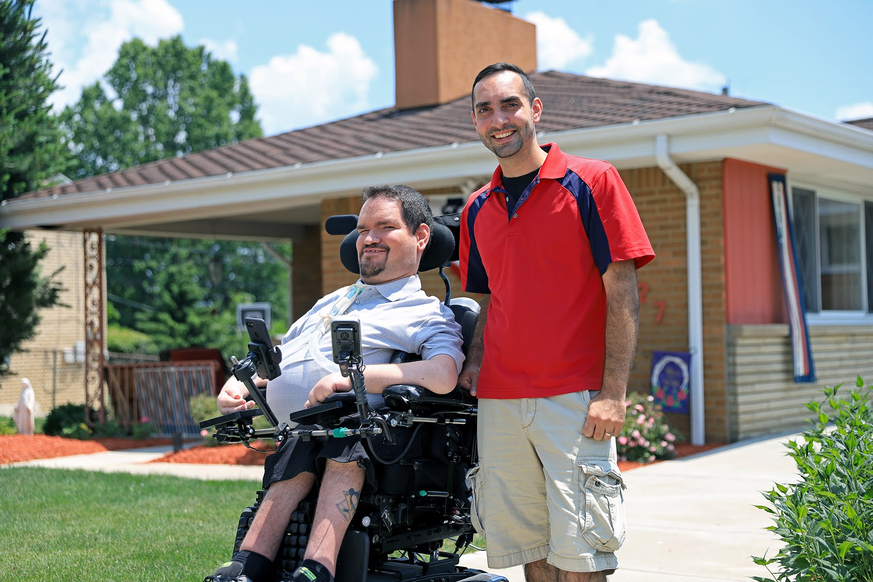 Photograph of brothers Nick and Eric Sinagra standing outside Nick's house. They're both smiling at the camera. Nick is sitting in a power wheelchair, and Eric is standing beside him.