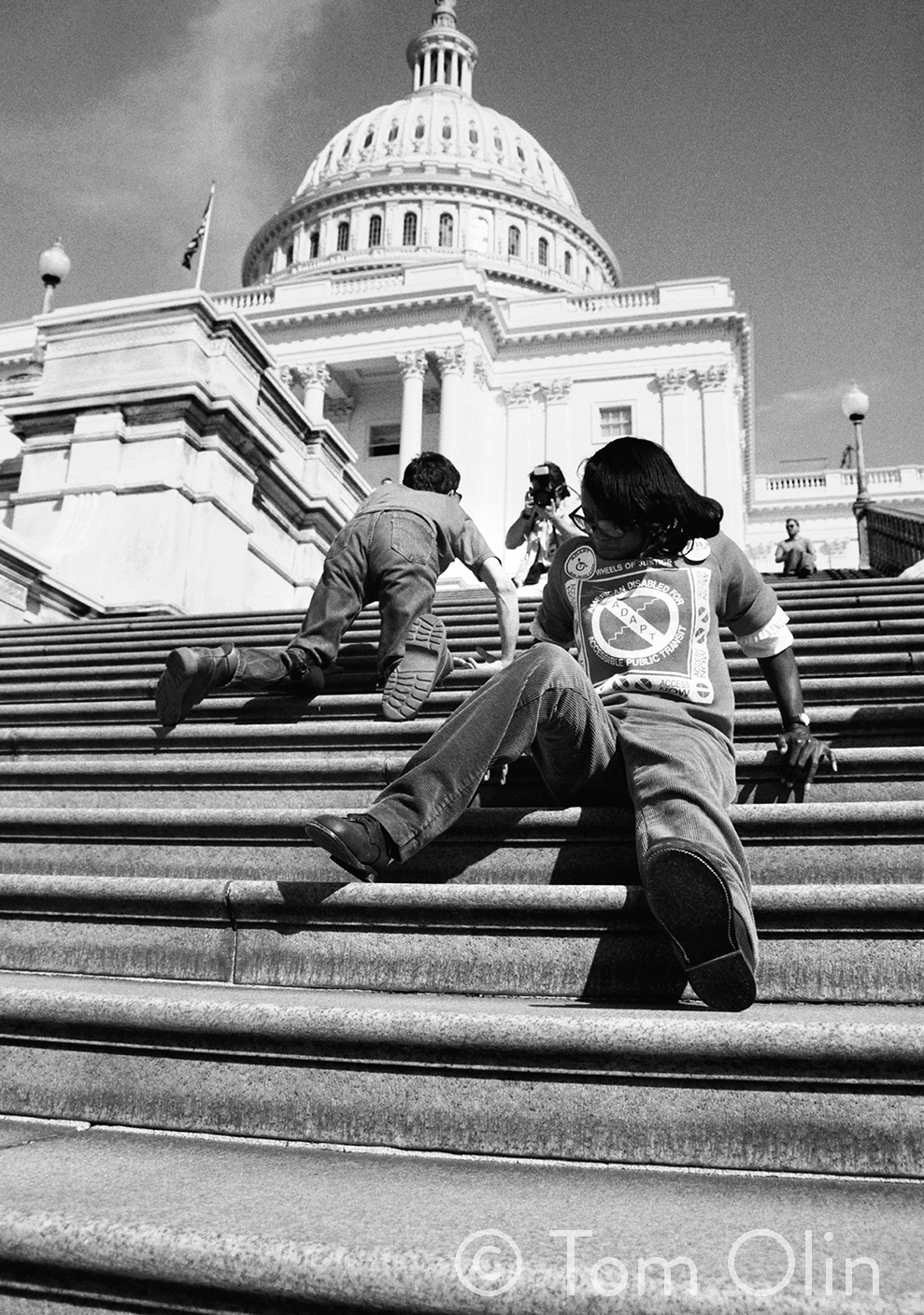 Black and white photograph of two disability rights activists. They are climbing the 83 steps up capitol hill. The photograph is shot from a low angle. In front, an activist is sitting and using their hands to push themself up the stairs backwards. In the background, another activist is crawling on his hands and knees.