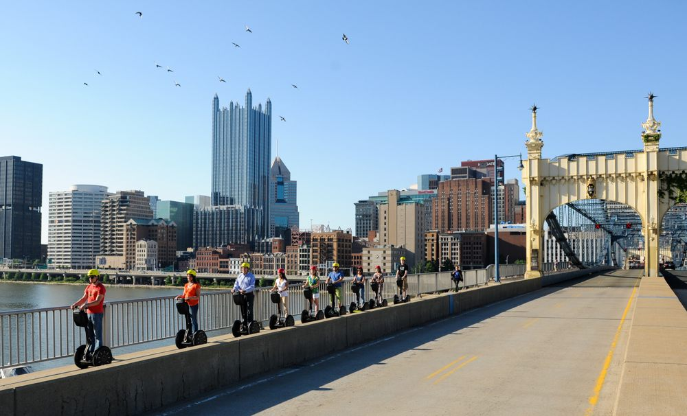 Wide shot photograph of a line of people riding segways. They're crossing a bridge in Pittsburgh. Behind them is Downtown Pittsburgh.