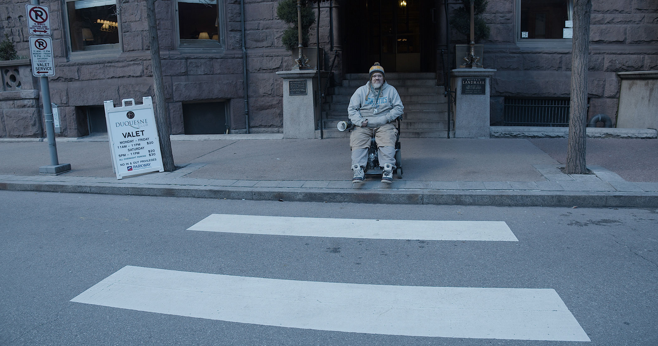 Zoomed out photograph of a man in a wheelchair on the sidewalk. He's waiting to cross at a crosswalk. The sidewalk below him has no curb cut.