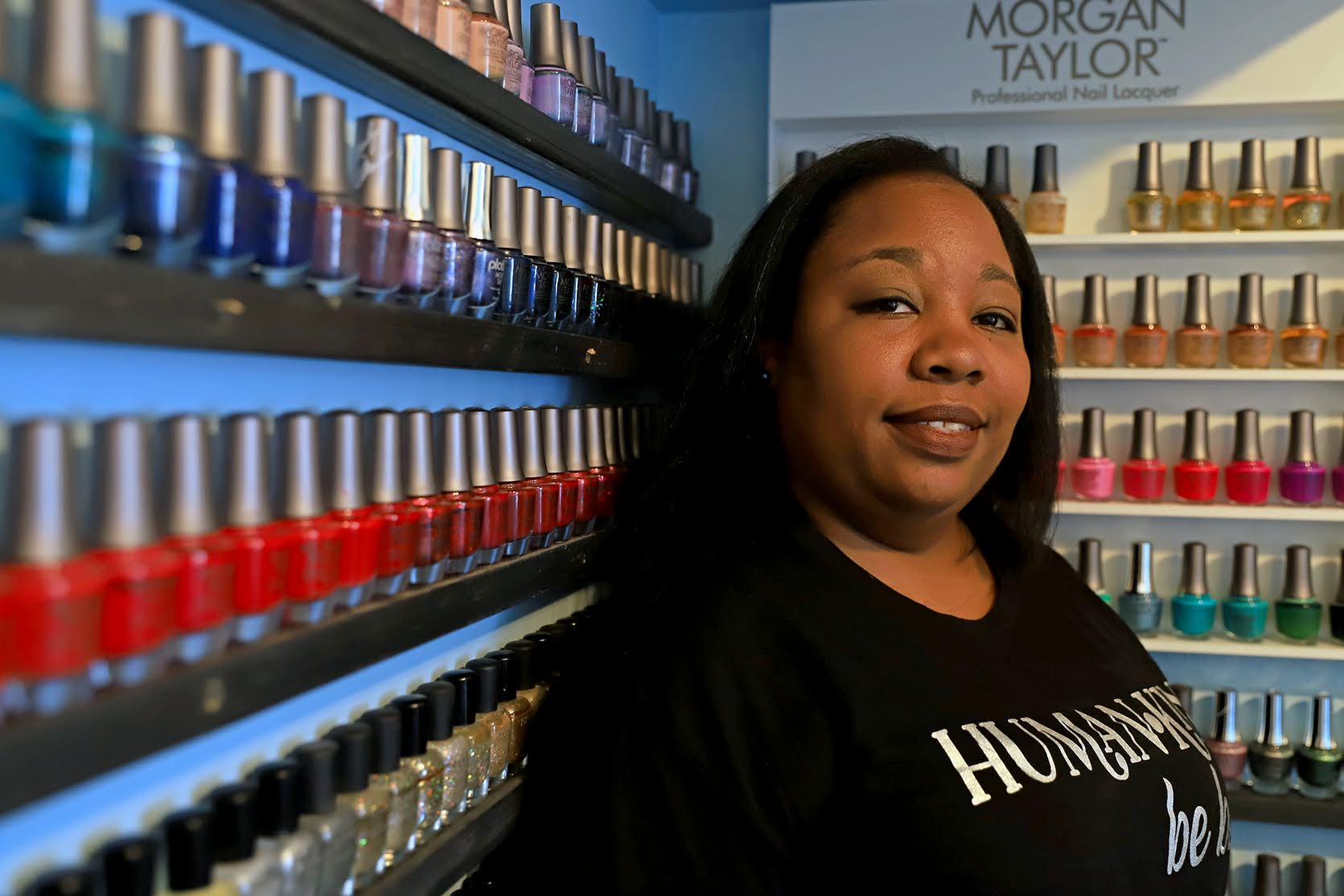 A Black woman stands in front of a row of nail polish colors.