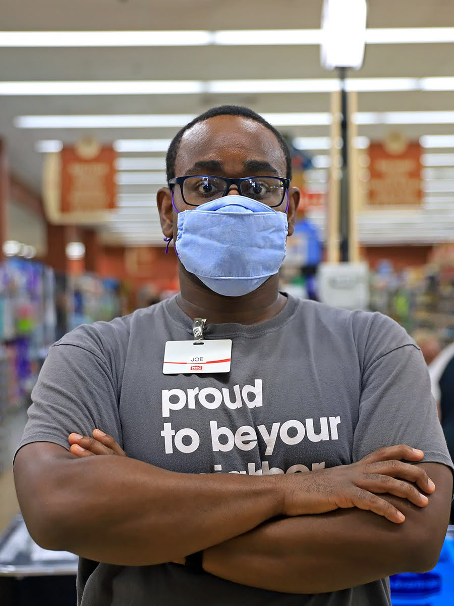 Photograph of essay author Joseph Vernon Smith. He is a Black man standing with his arms crossed looking at the camera. He wears a face mask and a Giant Eagle staff t-shirt that says proud to be your neighbor.