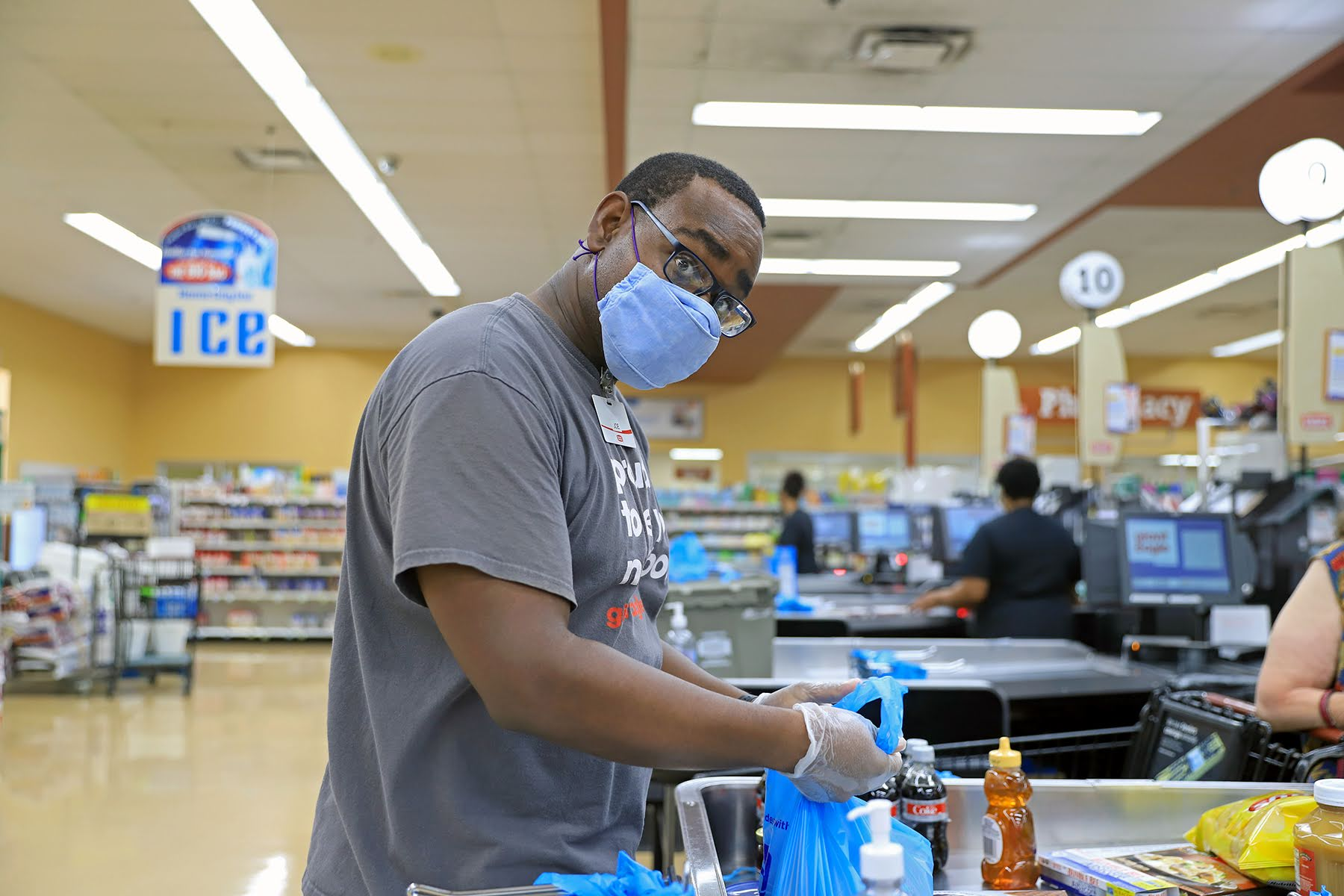 Joseph Vernon Smith, a Black man, bagging groceries at Giant Eagle. He's wearing a face mask and his head is turned to look straight at the camera.