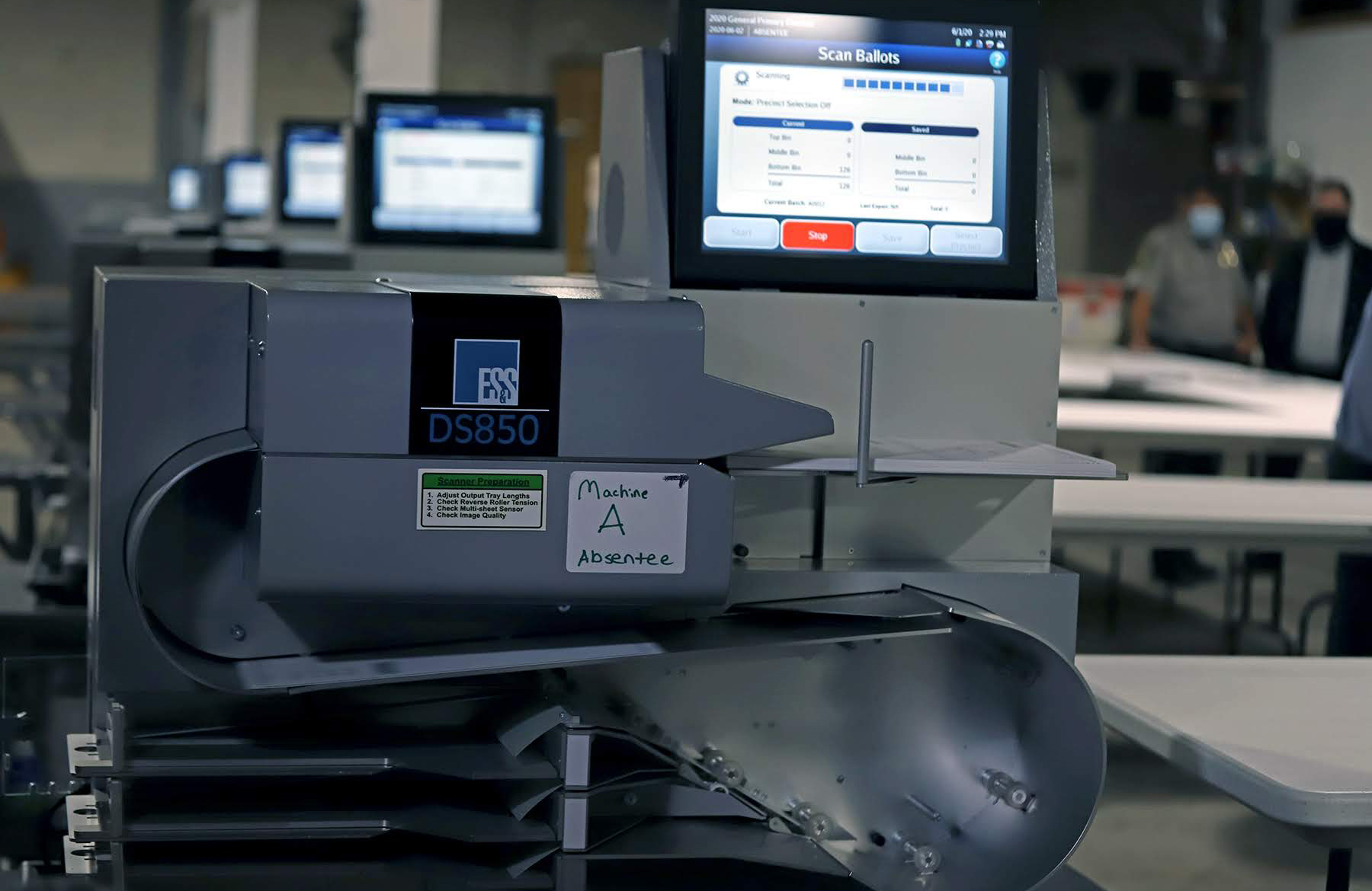 Photograph of a row of ballot scanning machines.