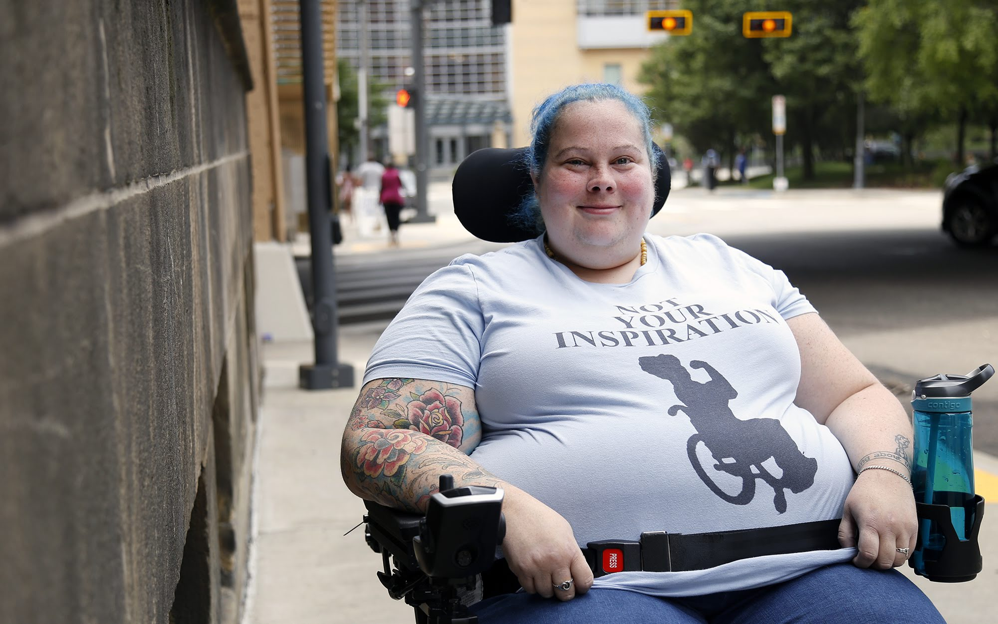 "Photograph of Alisa Grisham outside on the sidewalk with the street behind her. She is in her wheelchair and wearing a T-shirt that says ""not your inspiration"" and below it is a silhouette of a person in a wheelchair."