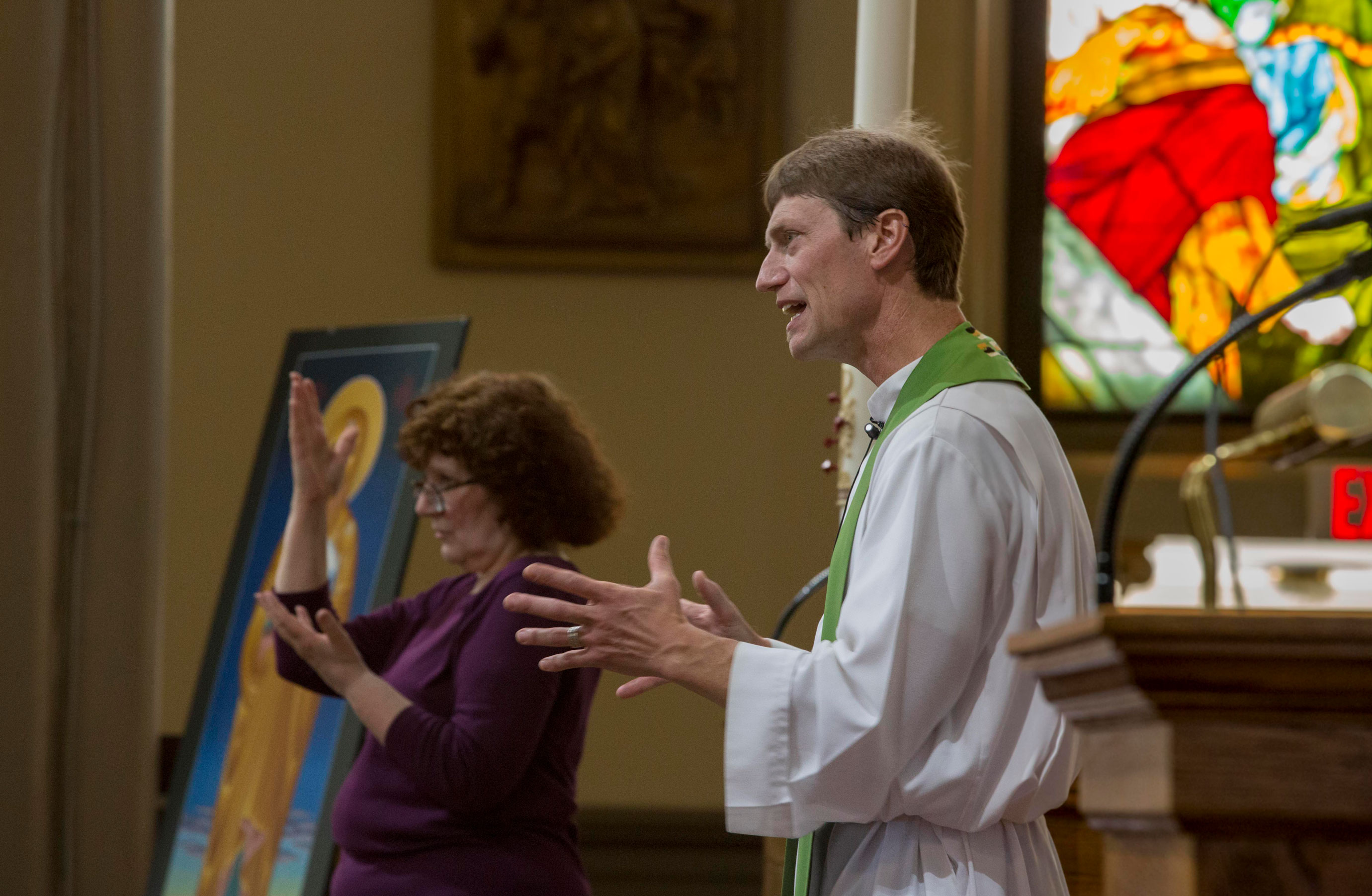 Photograph of a catholic priest delivering a sermon. He's inside a church in front of his congregation. In the background, a woman interprets his sermon in American Sign Language along with him.