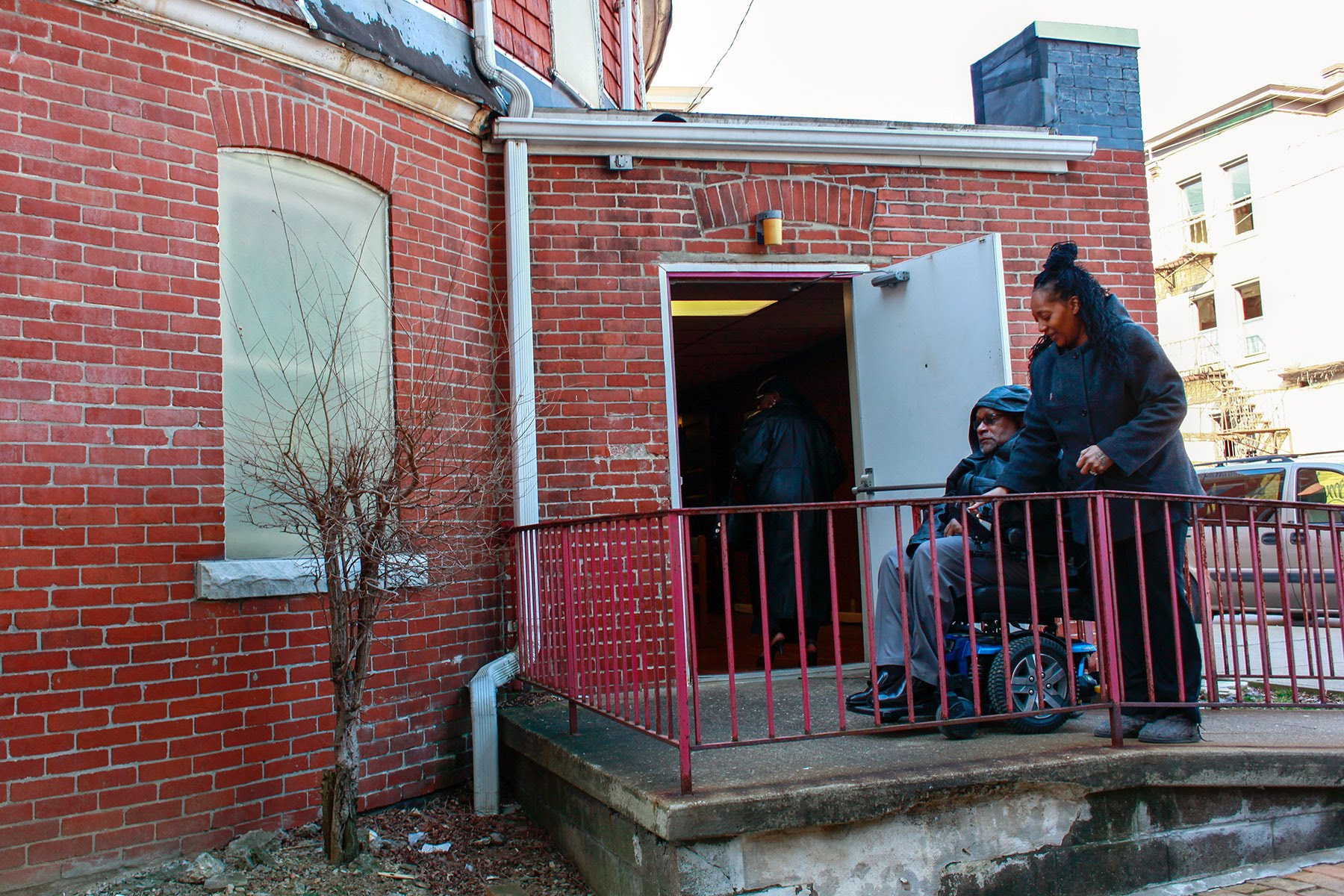 Photograph of an older Black man in motorized wheelchair going up a ramp into the back of a church. A younger Black woman walks beside him, helping him inside.